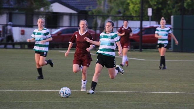 Villa Maria and Gannon graduate Kaitlyn Kissell, center, moves the ball past opponents during an Australia National Premier League game this season. Kissell plays for Souths United in Brisbane, Australia. She also works as a nurse for Health Care Australia.