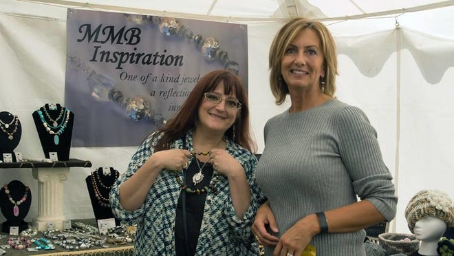 From left, Kim Holmes purchases jewelry from Sabina Bajiic's booth at last year's Madison County Craft Festival.