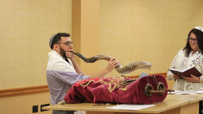 Jason Cook, an Ohio University Hillel rabbinic intern, blows the shofar, a musical instrument made from a ram's horn that is used for Jewish religious purposes, at Ohio University Hillel's Rosh Hashana event in 2019.