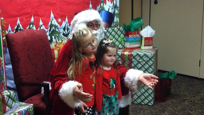 Lani Dirks, 5, and Cambrie Dirks, 3, meet Santa Claus during the Special Santa Event on Saturday in Des Moines.