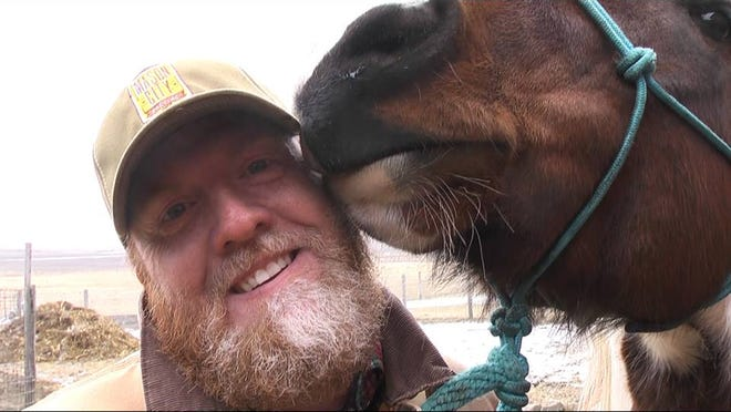 Mason City tap-room manager gets a smooch from an equine buddy.
