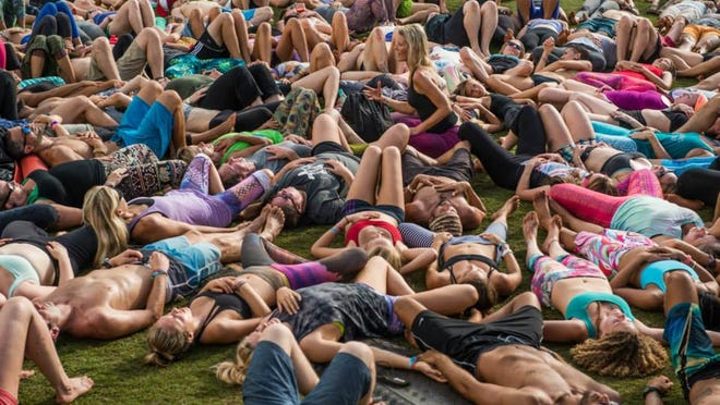 Wanderlust participants join in group meditation during a session in Hawaii. The Wanderlust 108 Triathlon combines a 5K, non-competitive run, a 90-minute yoga session and 30 minutes of guided meditation.
