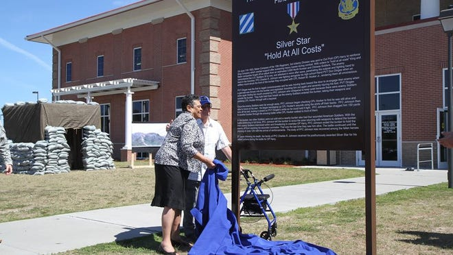 Juanita Mendez, 76, of Millbrook and Don Dingee, 82, of Tuscon, Arizona, stand next to a sign in front of the Pfc. Charles Johnson Fitness Center at Fort Stewart. The fitness center was dedicated to the fallen Korean War soldier and Arlington High School graduate on Tuesday.