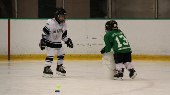 Learning to play hockey via the traditional rite of passage: the bucket. photo by Caurie Putnam