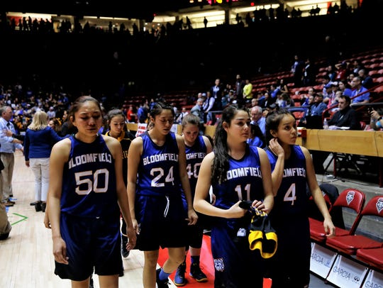 Bloomfield's Alyssa Quintana (50), Micaela Abeyta (24), Sidney Dugger (40), Lanay Gutierrez (11) and Madison Bedonie (4) fight back tears as they head to the locker room after losing to Los Lunas in Friday's 5A state championship game in Albuquerque.