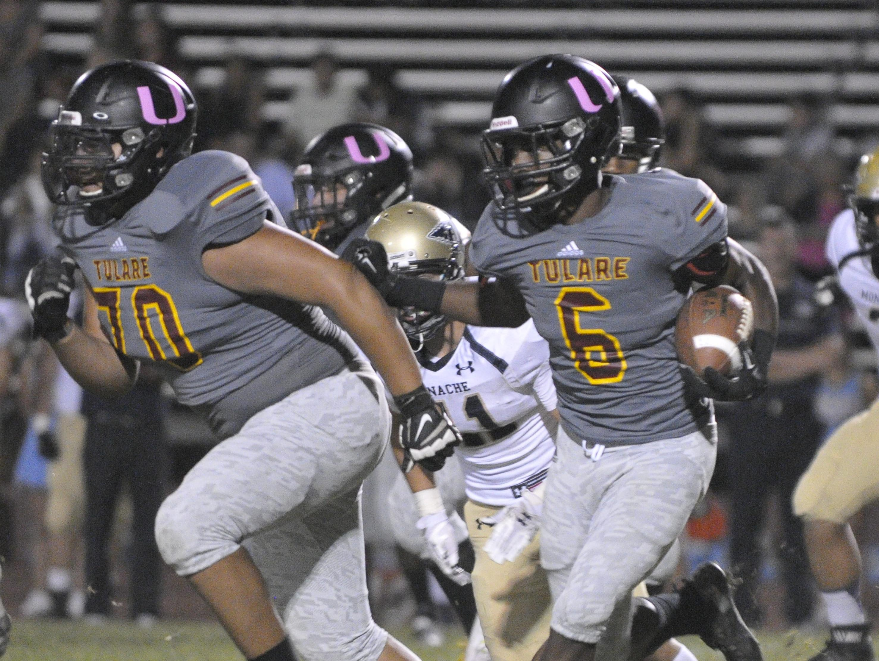 Tulare Union's Romeo Harris gets help from Ulisis Nunez as he runs the ball against Monache in an EYL game at Bob Mathias Stadium on Friday, October 9, 2015. Photo by Michael Alvarez Photo taken on 10/9/15 in Tulare, Ca. 1009_FBP_Monache-TU_0034 Camera data: 10/9/15 at 6:44:14 PM, ISO 4000, 1/400 @ f/2.8, WB=AUTO, 200mm, , FINE, frame 0034.
