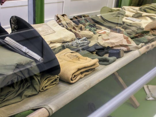A variety of military items are displayed in an exhibit