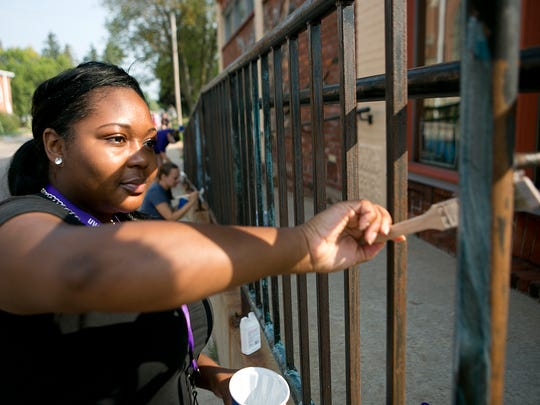 University of Wisconsin - Stevens Point freshman Patrice Williams, 18, helps prepare the railing for painting at the Stevens Point Area Co-op in Stevens Point, Tuesday, Sept. 1, 2015. Williams was volunteering with Labor of Love, which has UWSP students living in the residence halls providing local organizations with service activities.