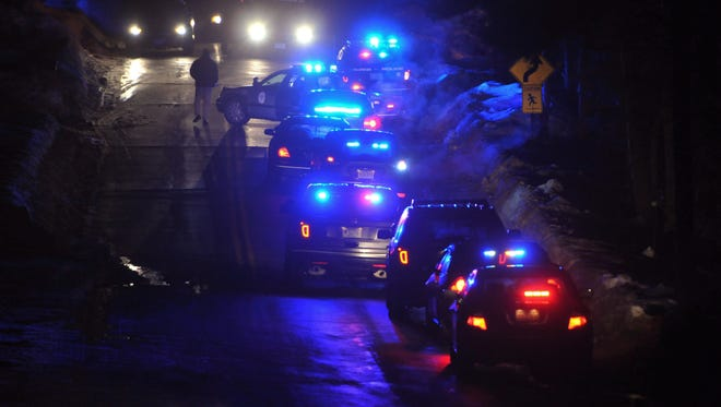 Police vehicles line a road leading to a Cape Cod condo community where one woman was shot to death and two other people, including a police officer, were wounded early Thursday, Feb. 5, 2015, in Bourne, Mass.