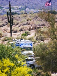 Police vehicles and yellow tape surround the site of