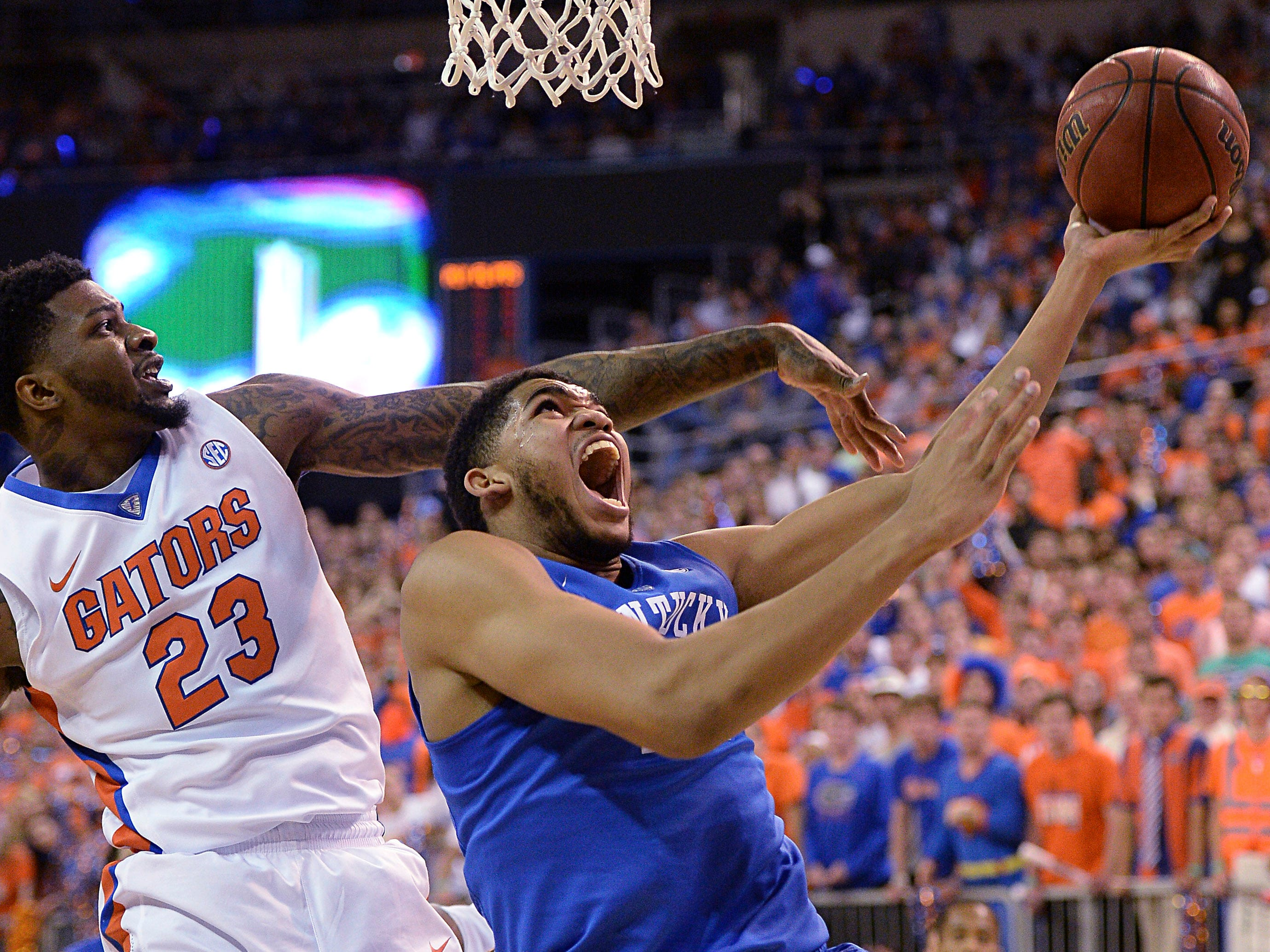 FIXES SCORE - Florida forward Chris Walker (23) pressures Kentucky forward Karl-Anthony Towns (12) during the first half of an NCAA college basketball game in Gainesville, Fla., Saturday, Feb. 7, 2015. Kentucky defeated Florida 68-61. (AP Photo/Phil Sandlin)