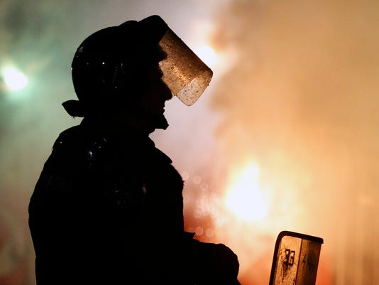 A Serbian riot police officer guards Red Star soccer fans light torches during a Serbian National soccer league derby match between Partizan and Red Star in Belgrade, Serbia, Wednesday, Dec. 13, 2017. (AP Photo/Darko Vojinovic)