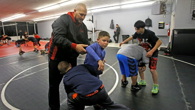 Levi Stout works with Tyse Darnell, right, and Cody Hargis Wednesday at the new Stout Wrestling Academy in Farmington.