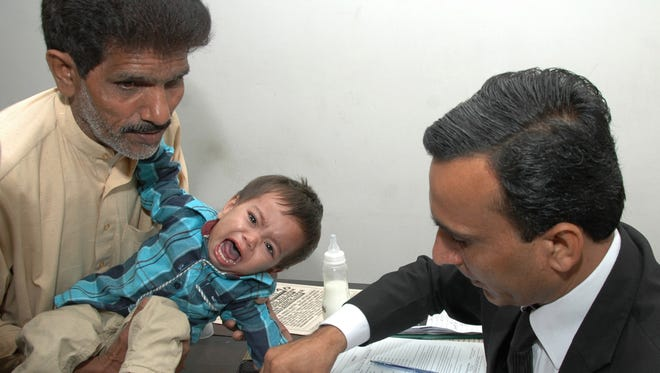 Held by his grandfather, Muhammad Musa Khan cried Thursday when he was fingerprinted in a Lahore, Pakistan, court before being released on bail on charges of attempted murder for being in a mob that threw stones at police.