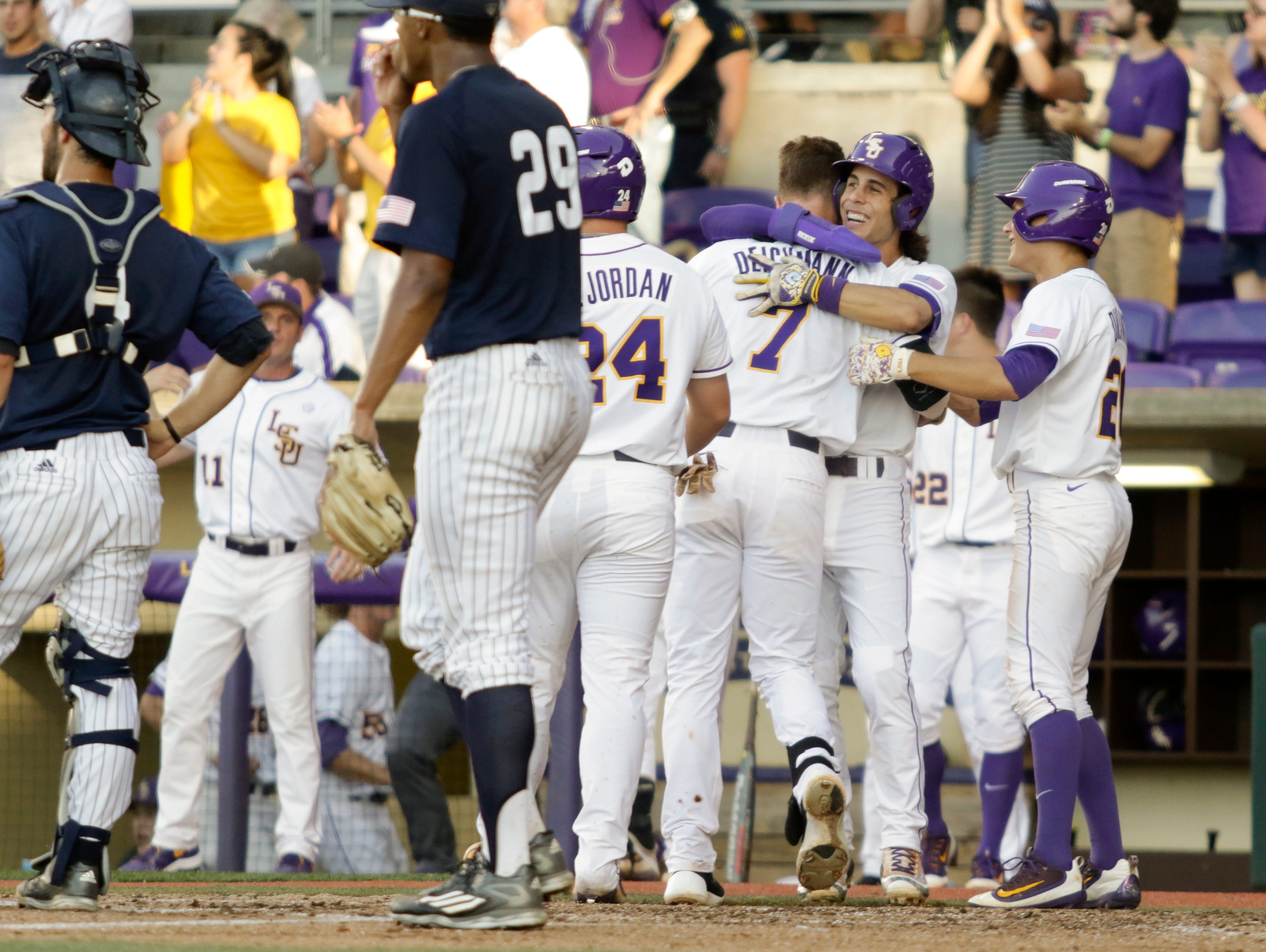 Greg Deichmann is greeted at home plate after hitting a bases loaded inside the park home run on Sunday at Alex Box Stadium in the Baton Rouge Regional of the NCAA Division 1 Baseball Championship.