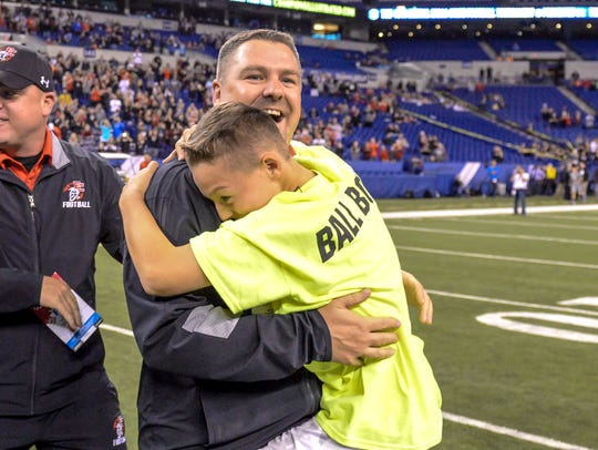 East Central head coach Justin Roden hugs his son