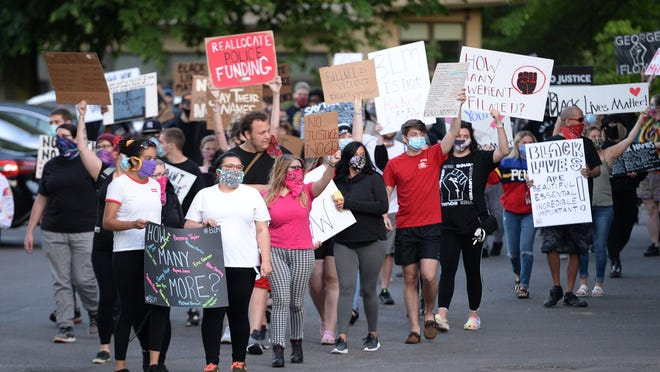 Members of Erie Equal march through Frontier Park on Tuesday. The group was protesting Erie Mayor Joe Schember's decision to suspend for three days an Erie Police officer caught on video kicking a seated protester during the downtown riot on May 30.