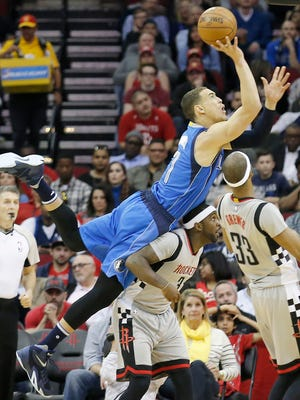 Dallas Mavericks forward Dwight Powell (7) shoots while laying on the back of Houston Rockets forward Sam Dekker (7) in the second quarter at Toyota Center.