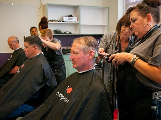 Army veteran David Smith, right, gets his hair cut at no cost by Vista College Director of Cosmetology Brenda Casavant and Vista student Rhonda Polanco during the Las Cruces Veteran's Stand Down event at Alma d'Arte Charter High School on Saturday.
