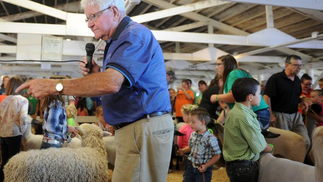 Darrel Cubbison, fair board president, instructs children during annual Pee Wee Sheep show at the Muskingum County Fair.