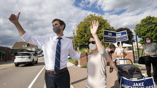 Jake Auchincloss, a Democratic candidate for the 4th Congressional District seat, and his wife, Michelle Gattineri, wave to supporters in Needham, Sept. 1, 2020.