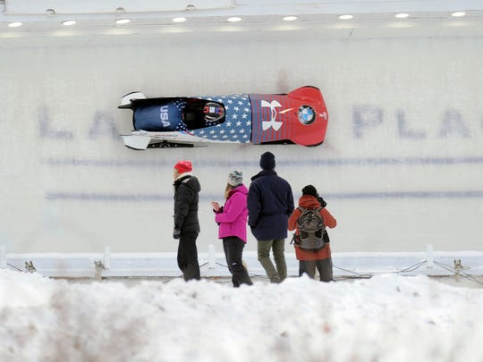 Fans watch the American team of Steven Holcomb and Sam McGuffie navigate the course during the men's two-man race at the bobsled World Cup event in Lake Placid, N.Y. Holcomb and McGuffie won as the U.S. swept the men's and women's races.