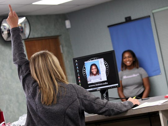 Alexi Gregory, 16, a junior at University High School in Ferndale, smiles as she gets her photo taken for her new Baker College school ID during the orientation at Baker College's Auburn Hills campus on Tuesday.