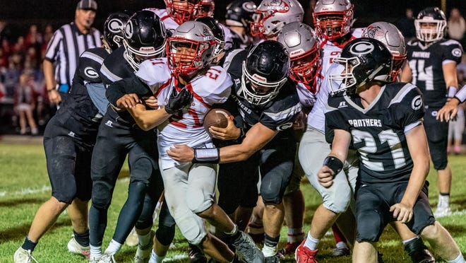 Mexico's Isaiah Reams (21) carries the ball against Centralia defenders during a game last season in Centralia.