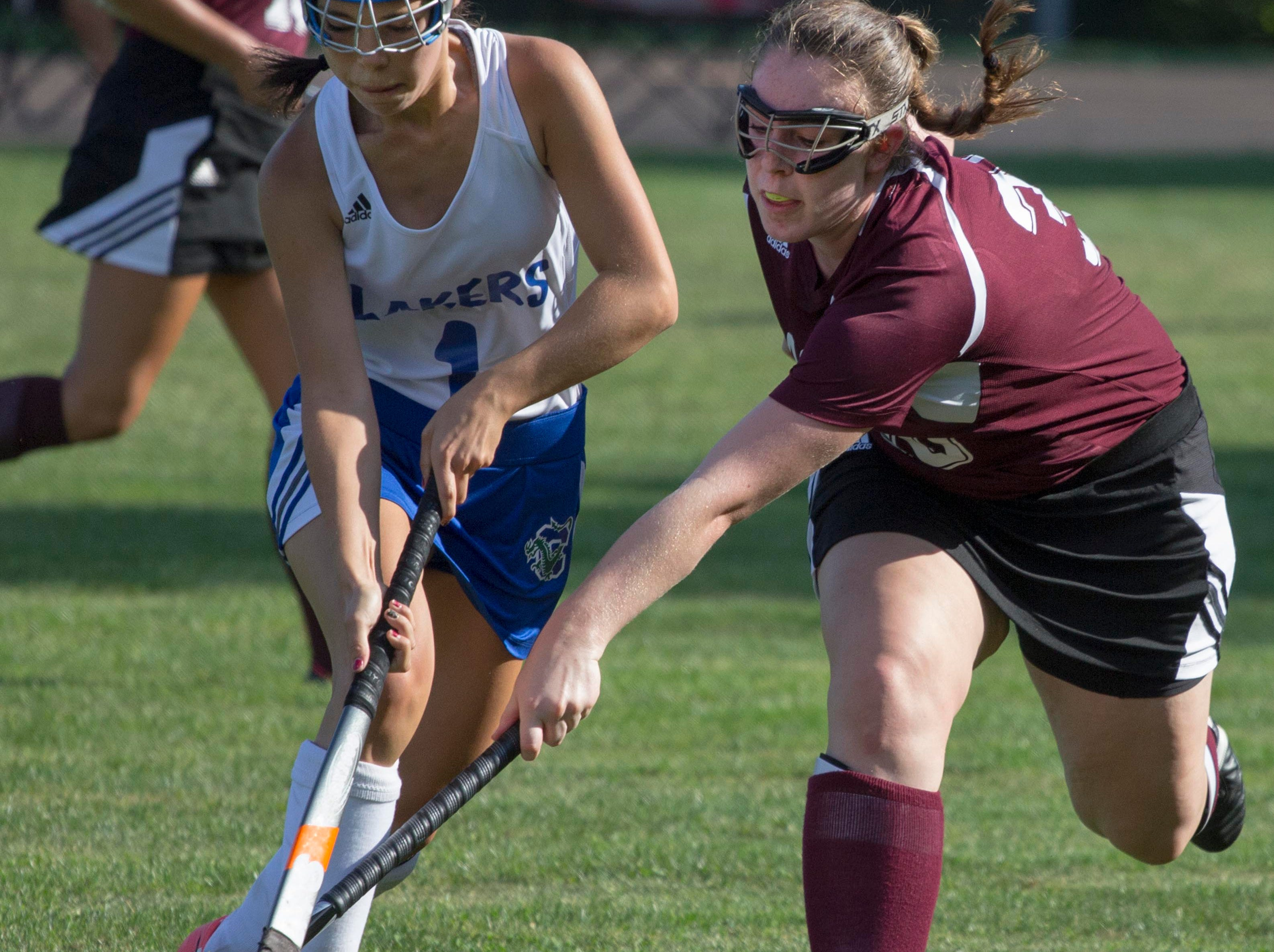 Mt. Abraham's Ellie Gevry, right, reaches in for the ball against Colchester's Erin Horton, left, during field hockey action at Colchester High School on Tuesday.