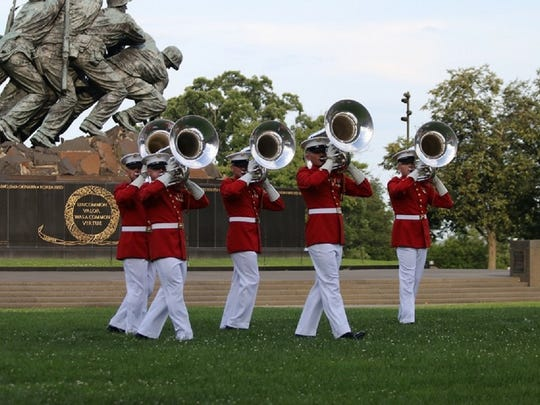 """The tuba section of """"The Commandant's Own"""" Drum and Bugle Corps, shown by the famous Marine Corps War Memorial (Iwo Jima Memorial) in Washington, D.C."""