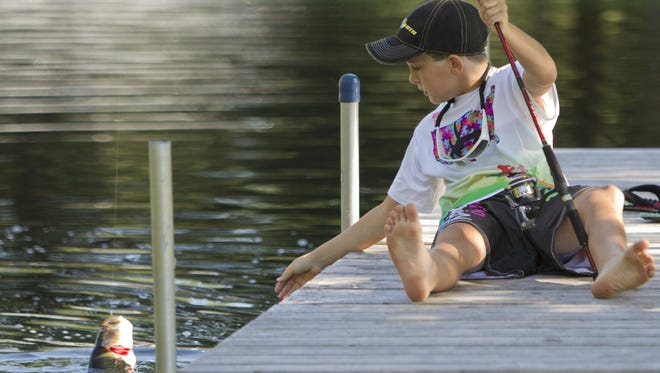 Remington Barkley, 11, pulls in a bass from the pond at the Barkleys' Hartland Township home.