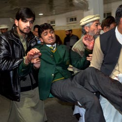Pakistani volunteers carry a student injured in the school massacre Tuesday in Peshawar.