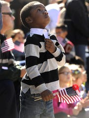 A youngster puts his hand over his heart during a recent Veterans Day parade through downtown Abilene.