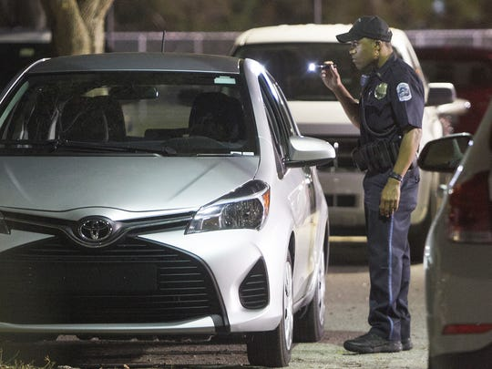 Police search the Fort Myers City of Palms Park parking lot for evidence after a shooting Tuesday evening.