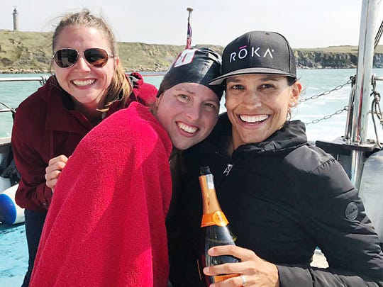 Heather Roka, center, a Fort Myers High graduate, celebrates swimming the English Channel on Friday morning. Roka completed the 21-mile swim from Dover, England to near Calais, France in 12 hours, 13 minutes and 53 seconds. She started at 8:04 p.m. EST, 1:04 a.m. in England.