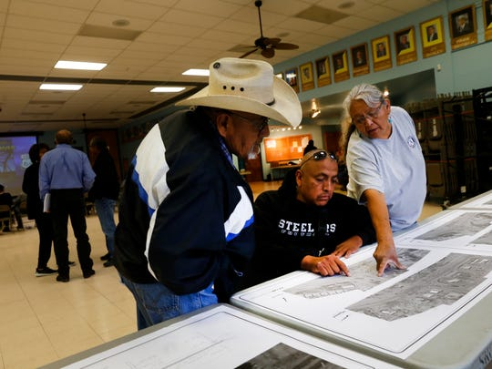 Nate Ellison, center, and Natalie J. Beyale, right, look over maps detailing options to renovate or replace the bridges and the intersections of U.S. highways 491 and 64 during a meeting Wednesday at the Shiprock Chapter house.