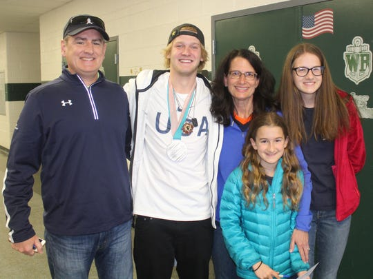 Kyle Mack (second from left) takes a photo with his second-grade teacher Dianne Colby (third from left) and her husband Ray (left) and children Caroline and Kathleen.