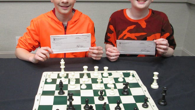 Augie and Jack Citrone display their prize-winning checks for their performance at the 62nd Maryland Open chess tournament.