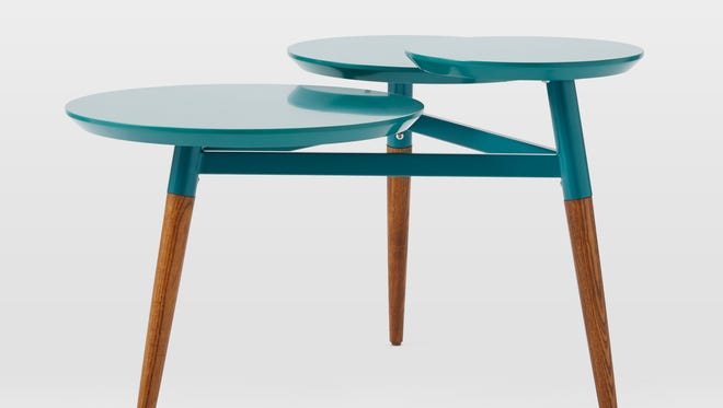 This photo provided by West Elm shows a Clover coffee table that takes an iconic midcentury shape and offers it in a variety of finishes, including teal blue. It is also available in red.  (AP Photo/West Elm)