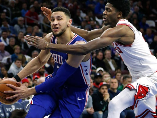 Philadelphia 76ers guard Ben Simmons (25), left, moves around Chicago Bulls guard Justin Holiday (7) during the second half on an NBA basketball game Wednesday, Jan. 24, 2018, in Philadelphia. The 76ers won 115-101. (AP Photo/Laurence Kesterson)