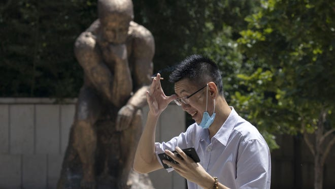 A man lowers his mask to smoke as he passes by a statue in the likeness of The Thinker in Beijing, China on Monday, July 6, 2020.
