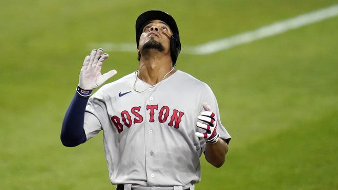 Boston Red Sox's Xander Bogaerts reacts after hitting a solo home run off Baltimore Orioles starting pitcher John Means during the second inning of a baseball game, Friday, Aug. 21, 2020, in Baltimore.