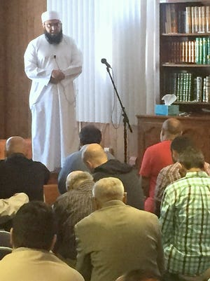 Imam Hafiz Wali Ullah leads a prayer during a memorial service Friday for boxing great Muhammad Ali at the Islamic Association of the Finger  Lakes in Big Flats.