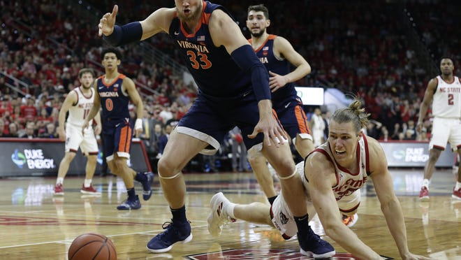Virginia's Jack Salt, left, and North Carolina State's Wyatt Walker reach for a loose ball during the first half Tuesday. No. 3 Virginia won 66-65 in overtime.