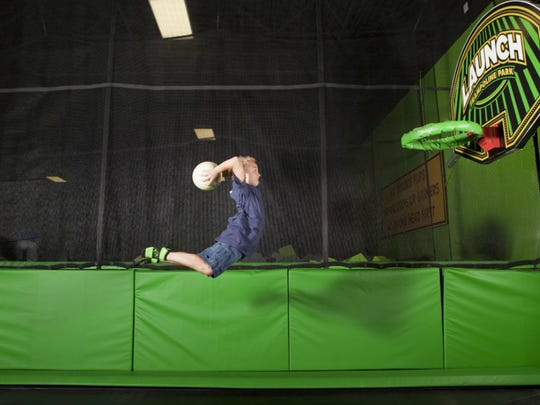 A child tries to make a goal at a basketball dunking lane at a Launch Trampoline Park. This summer, the Launch Trampoline Park of Asheville will open in Arden.