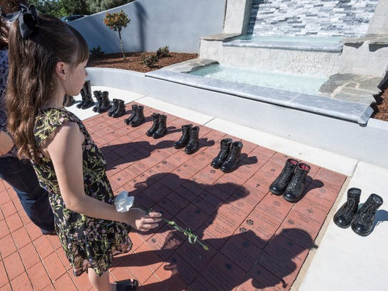 Hayley Ballantyne, 11, pauses with boots representing