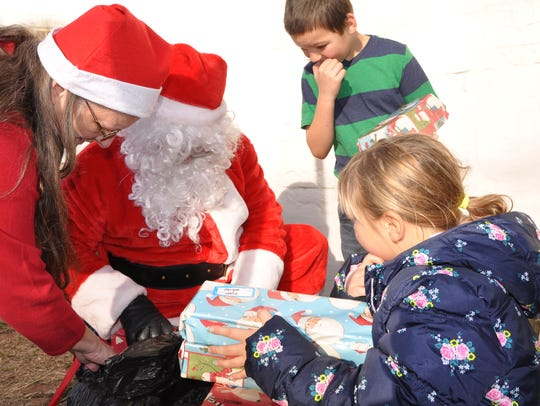 Jody Eyer plays Santa and delivers presents as part