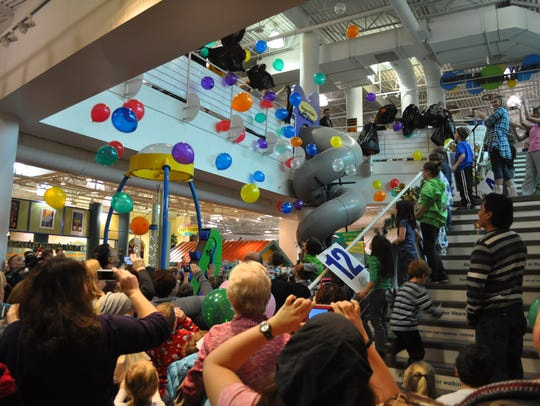 Balloons drop from the second floor of Discovery Center