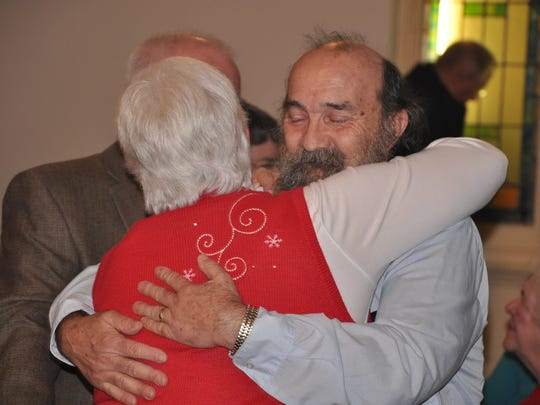 Members of the congregation hug following the final service at St. John's Lutheran Church on Sunday.