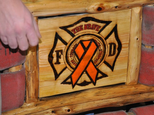 This firefighters emblem is the centerpiece of the fire-hose bench made to benefit the family of Todd Sites, a Marion firefighter diagnosed with acute leukemia.